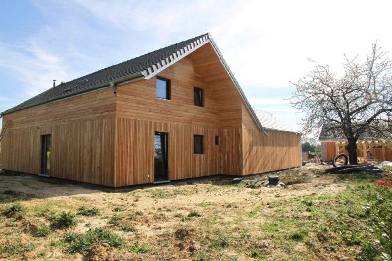 Vue extérieure d'une maison à ossature en bois. Joli design de cette maison avec un toit à pignon. Il se compose d'un revêtement partiel en gris et du reste en rouge, ce qui apporte de l'originalité à la construction.