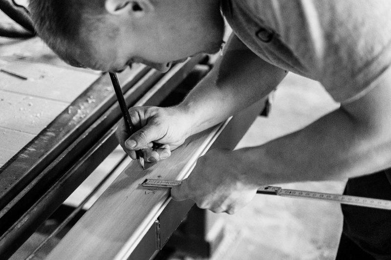 Un artisan en train de tracer des repères sur le bois