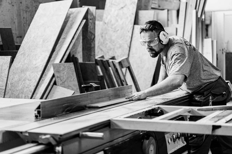 Un artisan en train de faire une découpe de planches de bois