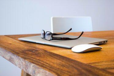 Ordinateur et lunettes posés sur une table fabriquée en bois