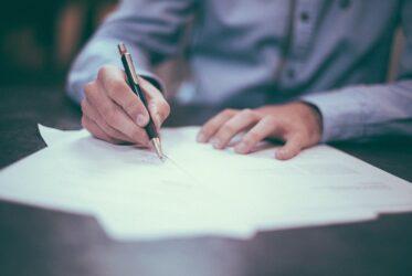 Une personne en train d'écrire sur une feuille de papier
