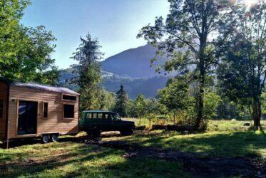 Tiny House Colibri tractée par un véhicule sur un terrain forestier